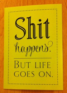 Postkarte mit dem Text: Shit happens. But life goes on.