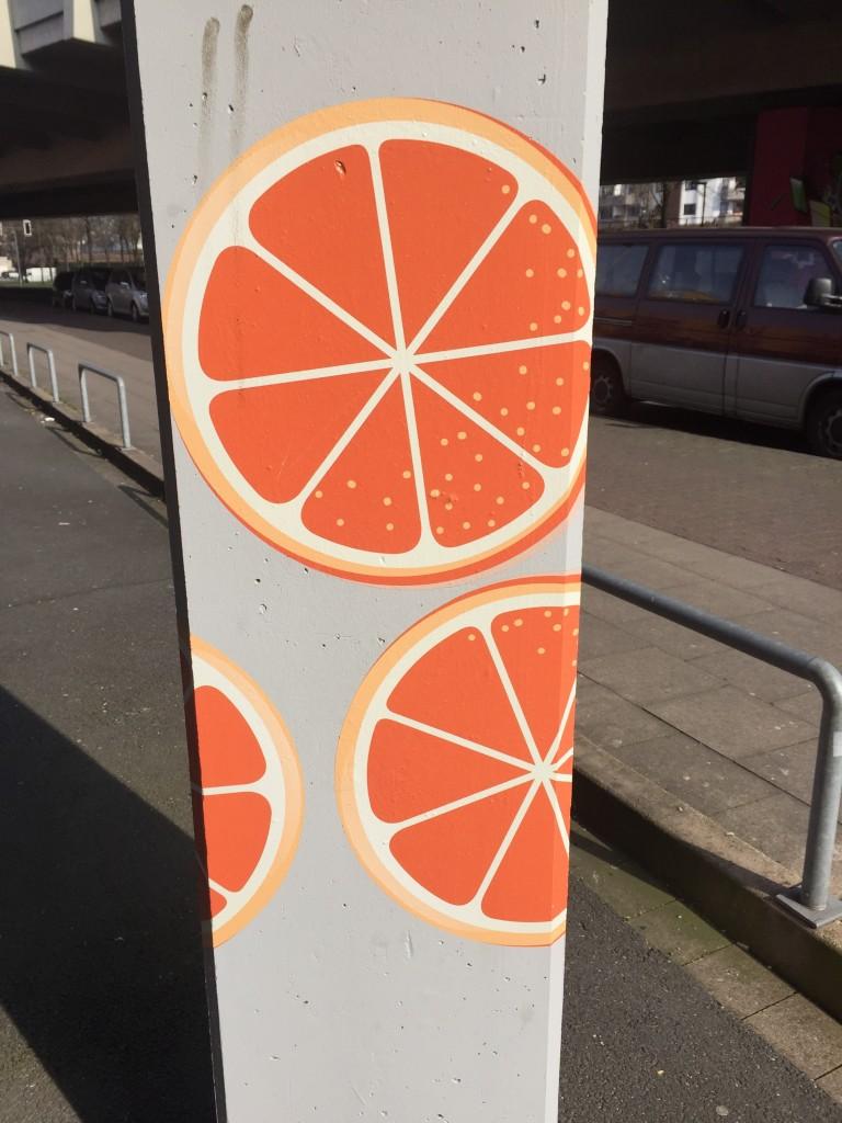 """Pfeiler der """"Orangenkiste"""" (Studentenwohnheim) in der Bielefelder Innenstadt, die mit Orangenscheiben bemalt wurden."""