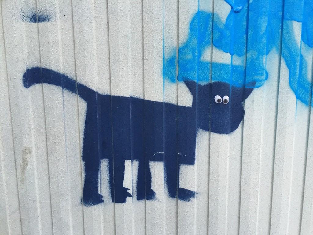 Blaue Grafitti-Katze mit aufgeklebten Wackelaugen.