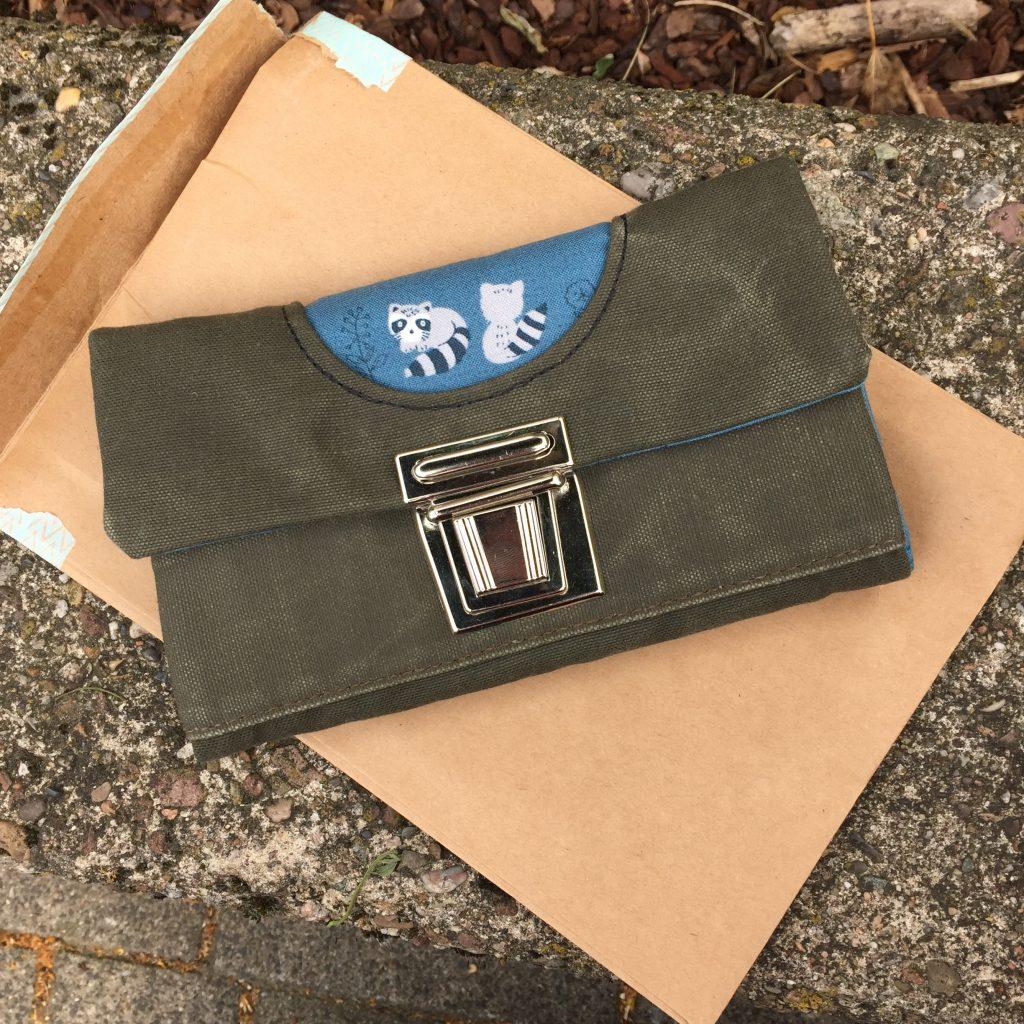 Portemonnaie von re.galerie - hergestellt aus einem Seesack und einem blauen Stoff, auf dem kleine Waschbären abgebildet sind.
